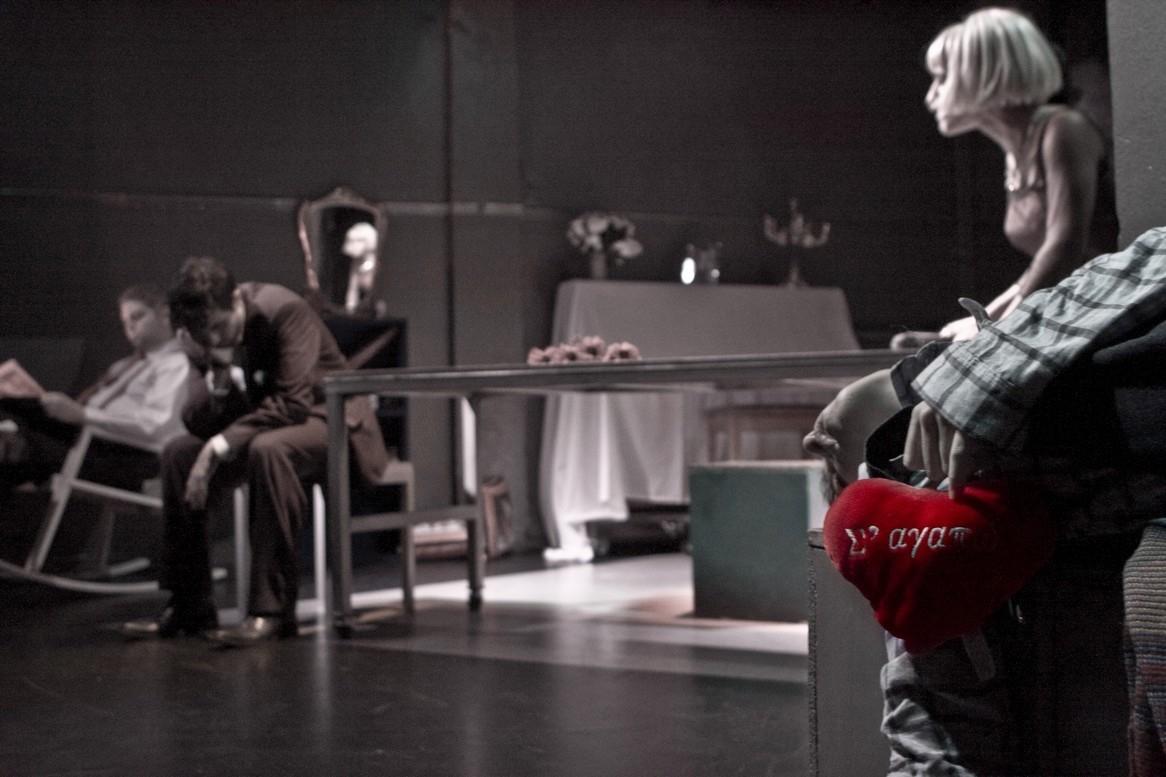 Δύο άντρες και μια γυναίκα κάθονται, ένα χέρι κρατάει μια καρδιά που γράφει «Σ' αγαπώ»